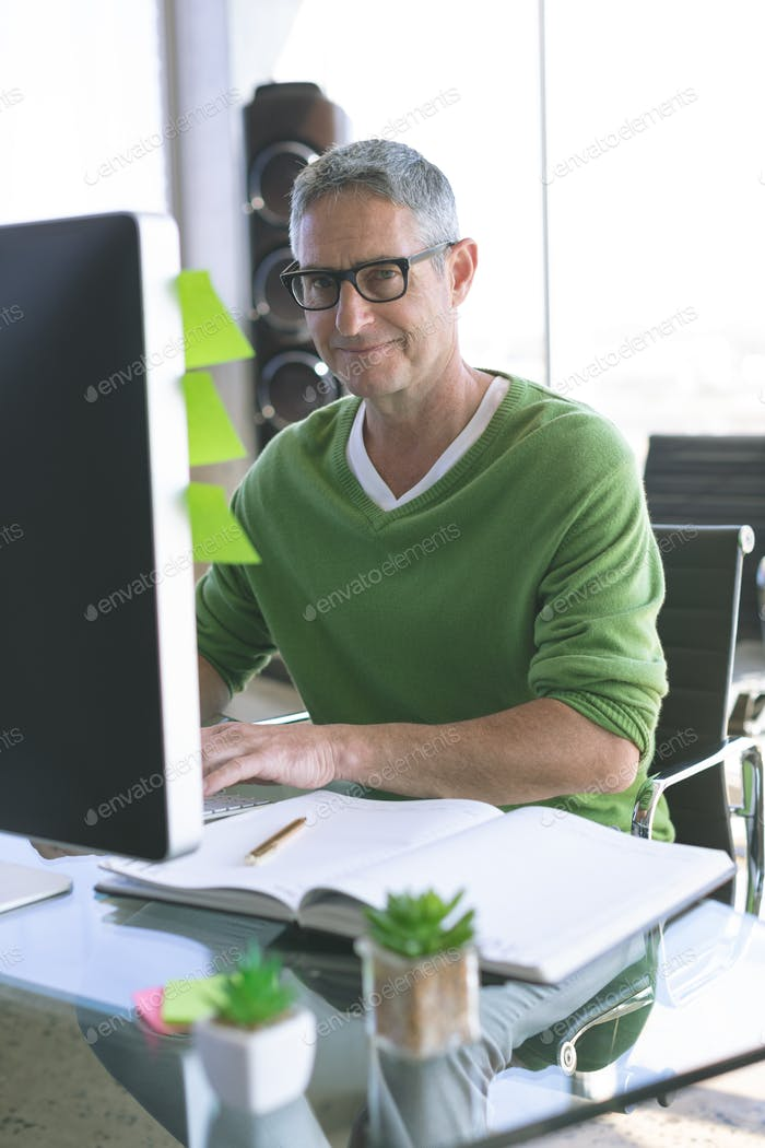 Businessman working on computer at desk in modern office