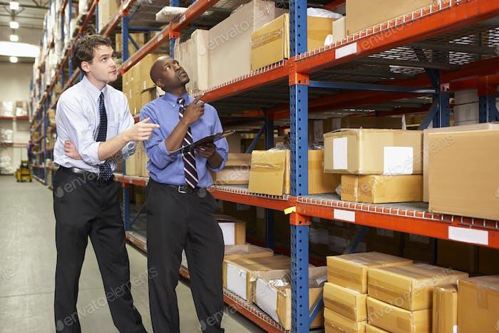 Два бизнесмена с буфер обмена на складе