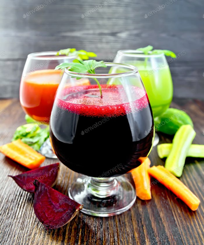 Juice beet and cucumber in wineglass on board