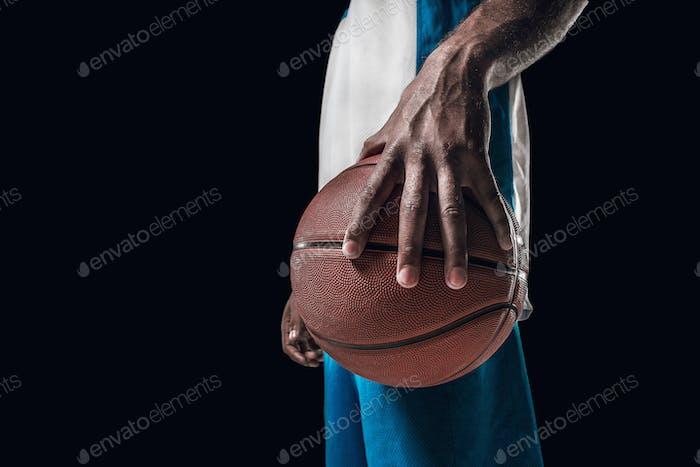 Das Porträt eines Basketballspielers mit Ball