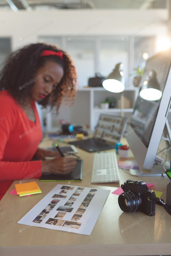 Young female graphic designer using graphic tablet at desk in a modern office