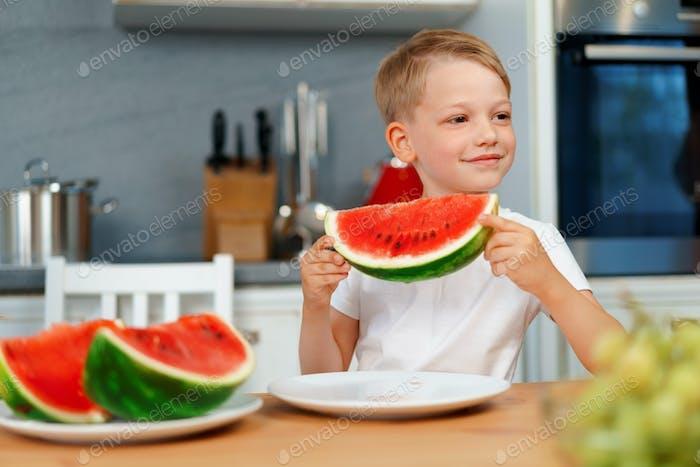 Kleiner Junge isst Wassermelonenstück in der Küche