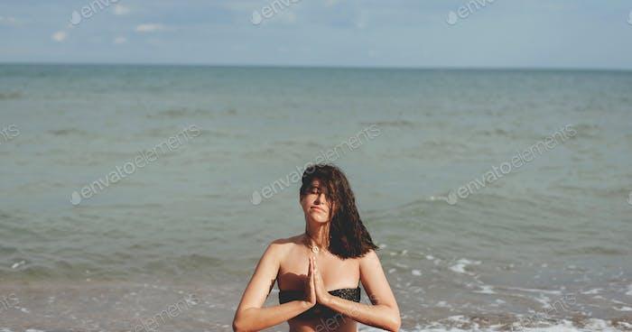 Junge schöne Frau praktiziert Yoga am Strand, sitzt auf Sand und meditieren