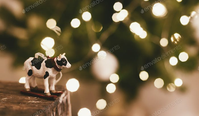 Cow or bull toy on background of beautiful christmas tree lights