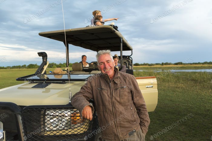 Ein lächelnder Safariführer und Familie von Touristen in einem Safarifahrzeug.