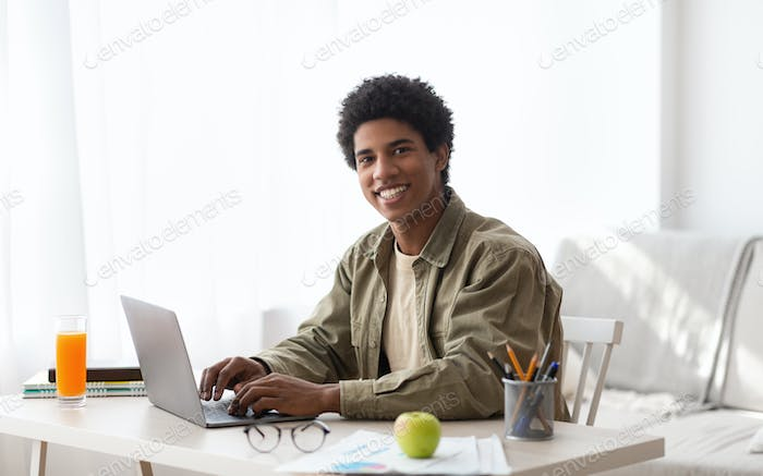 Remote schooling concept. Black teen guy typing on laptop computer during his online studies at home