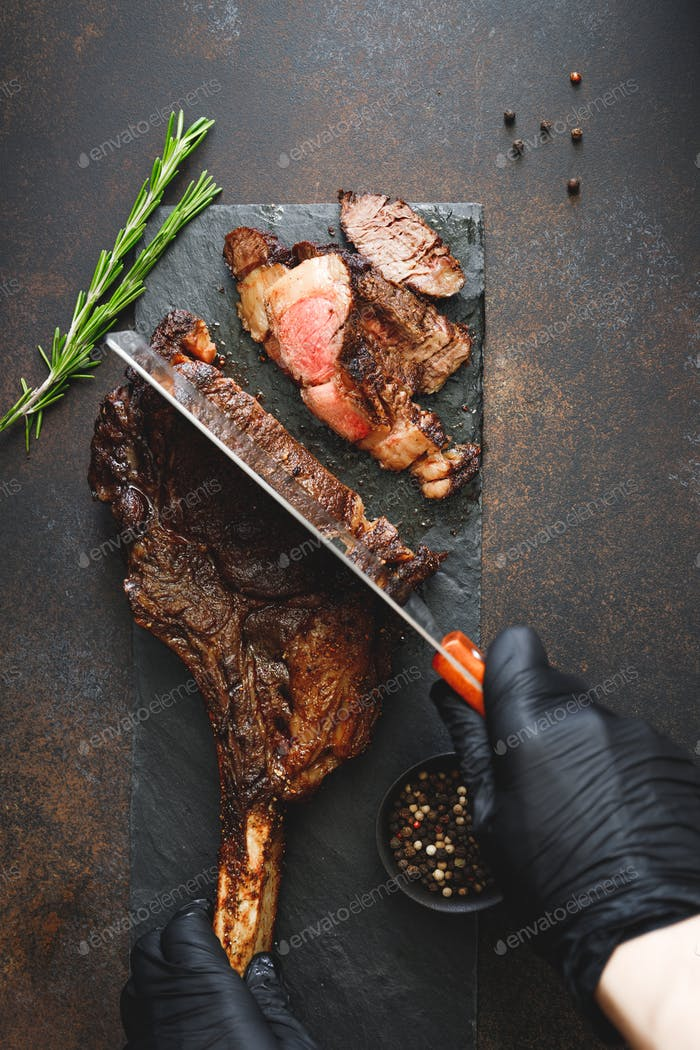 Man in black gloves cuts grilled marble beef steak Tomahawk. Top view, dinner concept.