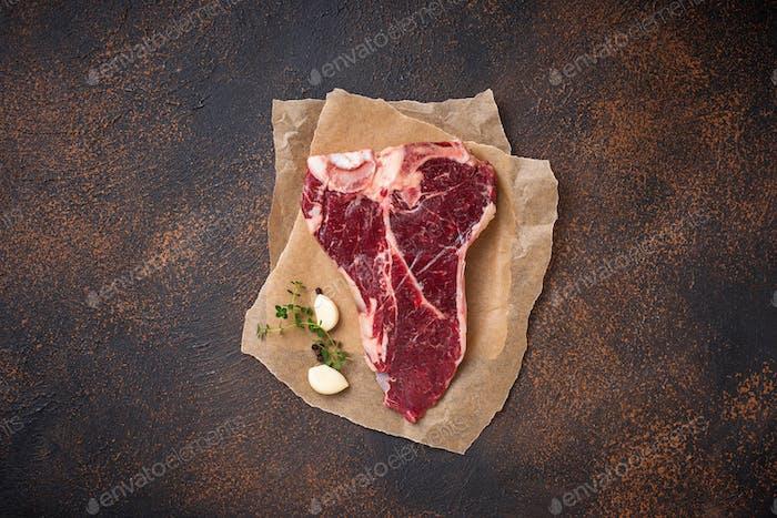 Raw T-bone steak with garlic and thyme