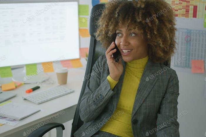 Fröhliche elegante Arbeiter im Gespräch am Telefon