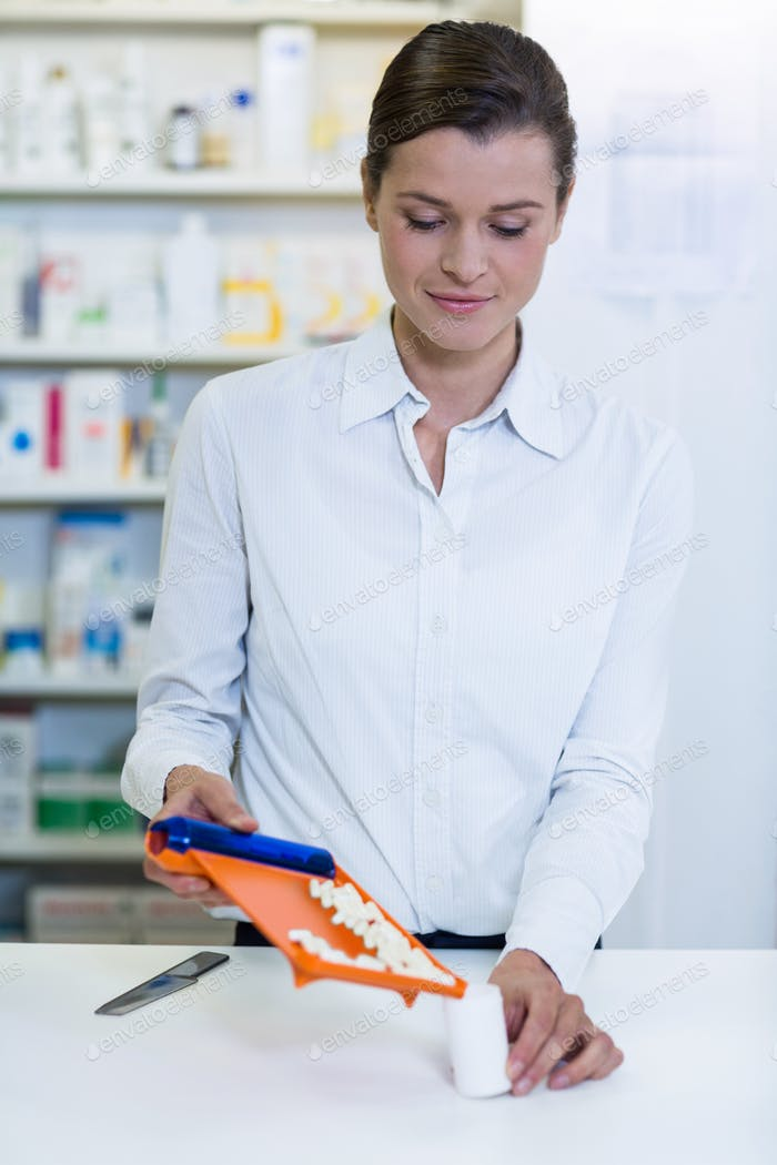 Pharmacist putting pill in container