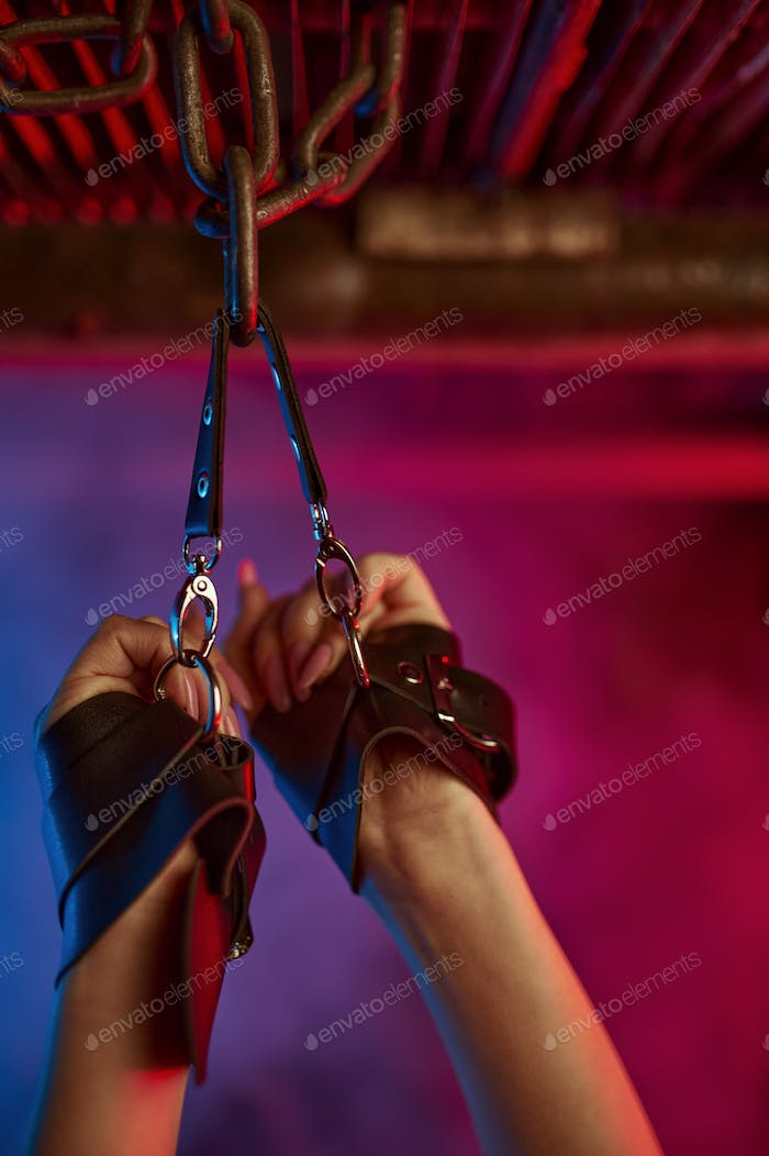 Female hands in leather bdsm handcuffs, fetish