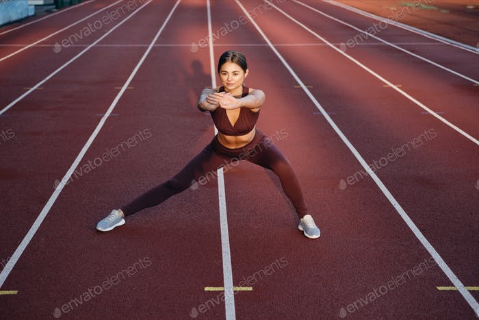 Beautiful sporty girl in sportswear doing stretching exercises on city stadium