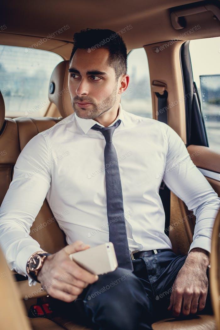 Стильный мужчина в белой рубашке с помощью смартфона.