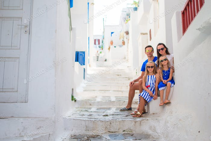 Family vacation in Europe. Parents and kids at street of typical greek traditional village on