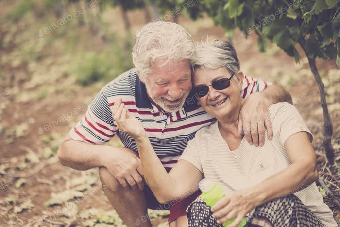 senior adult couple laugh in happines together forever playing with soap bubbles