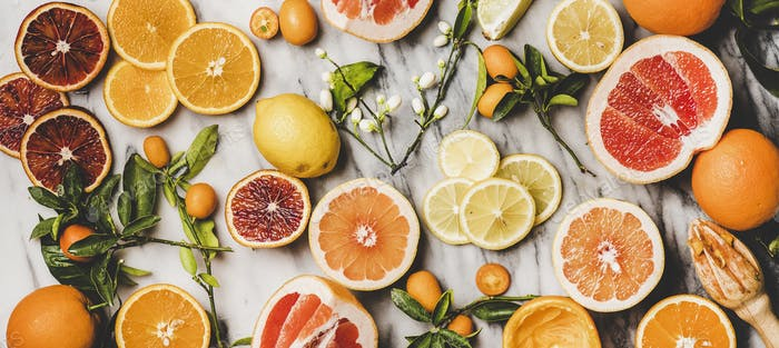 Flat-lay of fresh oranges, lemons, kumquats, grapefruits, wide composition