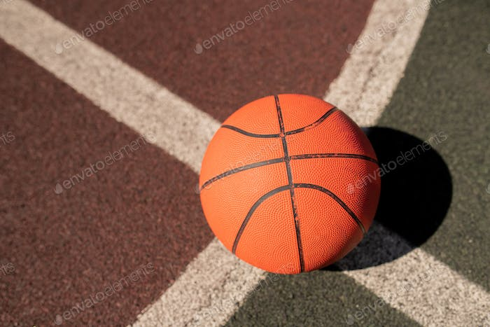 Overview of basketball gear on crossing of two white lines on stadium