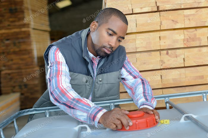man turning top of large container