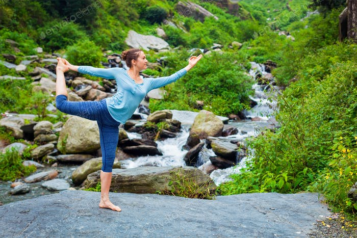 Woman doing yoga asana outdoors at waterfall