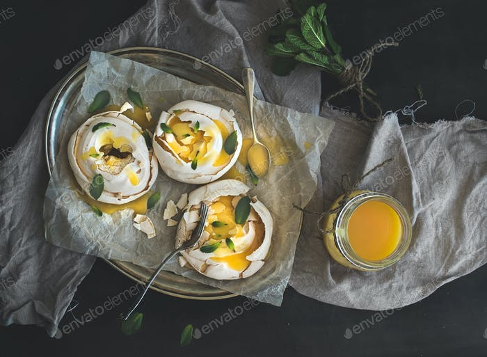 Merengues with lemon curd, fresh mint on silver tray, beige kitchen towel