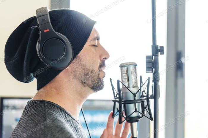 Junger Mann singt mit Mikrofon.