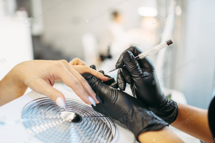 Beautician in gloves sticks nails of the client