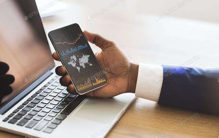 Hombre de negocios negro que comprueba el análisis financiero global en el teléfono inteligente o el comercio en divisas