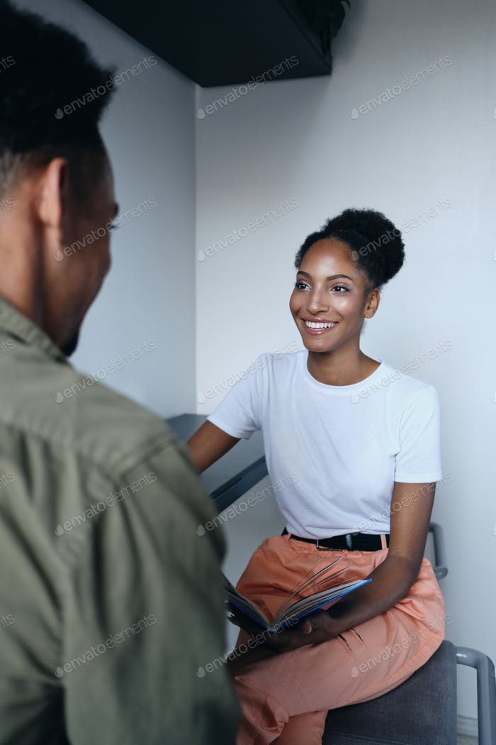 Young pretty casual African American woman happily talking with co worker in modern office