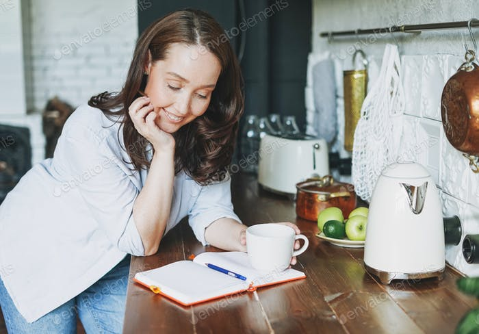 Adult smiling brunette woman in casual doing notes in daily book with cup of tea on kitchen
