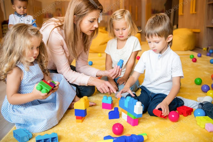 tutor and multicultural kids playing with constructor in kindergarten