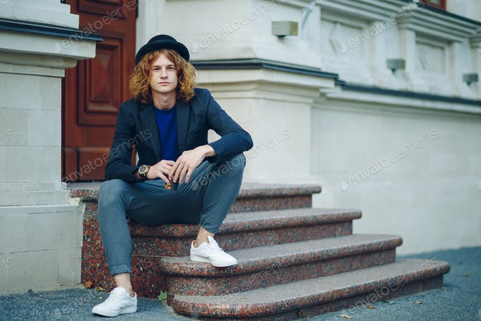 Red haired hipster man sitting on stairs thinking