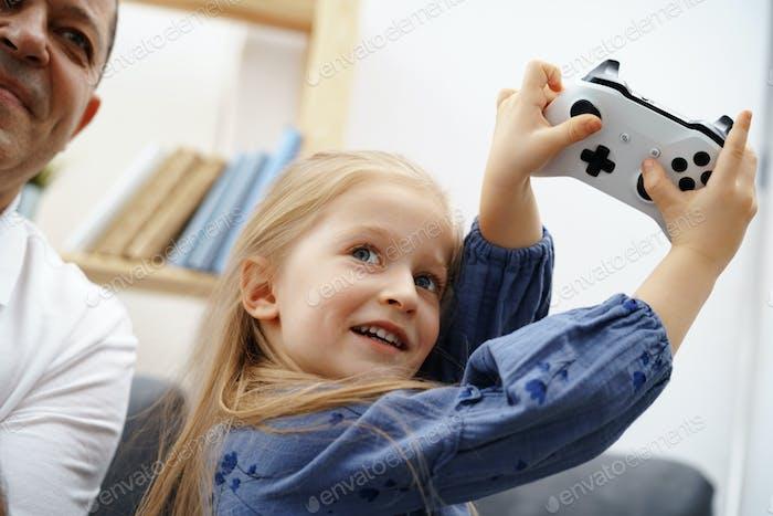 Дедушка и внучка играют в видеоигры дома