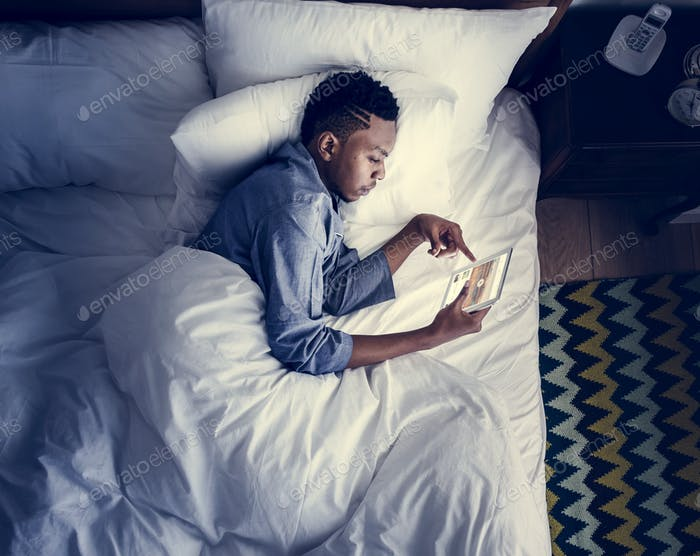 Man in bed using a digital device in the dark