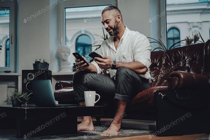 Emprendedor caucásico con dos teléfonos móviles en el apartamento