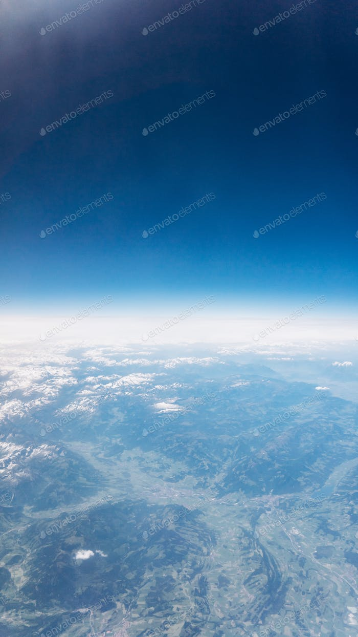 Top view of mountains with snow and clouds. View of the Alps.