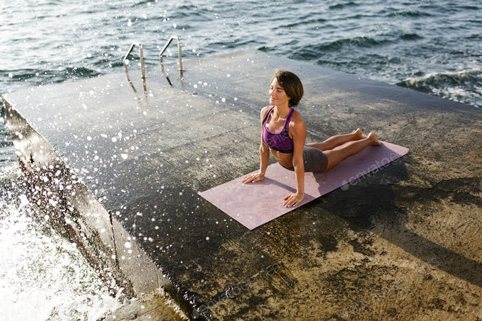 Smiling lady in sporty top and shorts practicing yoga with sea on background