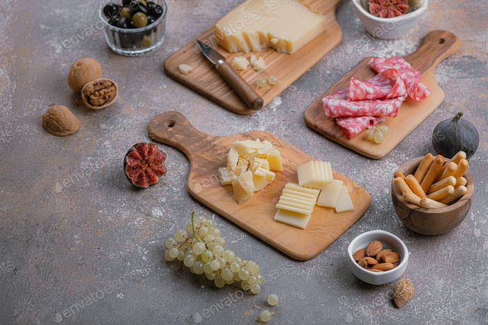 Assorted cheese, salumi, nuts on wooden boards, copy space