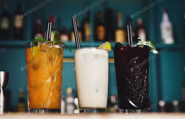 Creative exotic alcohol cocktails in night club bar