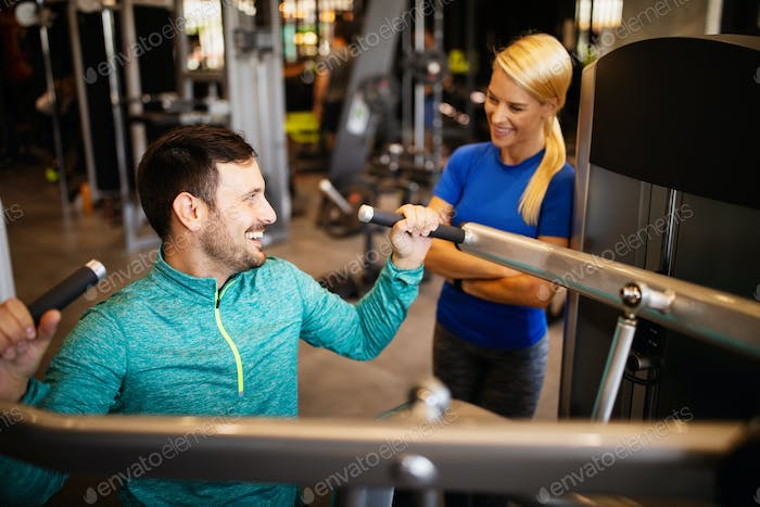 Happy fit man with his personal trainer doing exercise at the gym