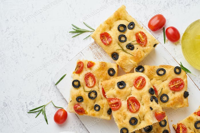 Sliced pieces of focaccia with tomatoes, olives and rosemary.