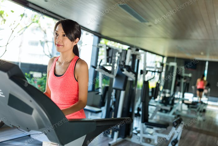 Woman running on on treadmill in gym