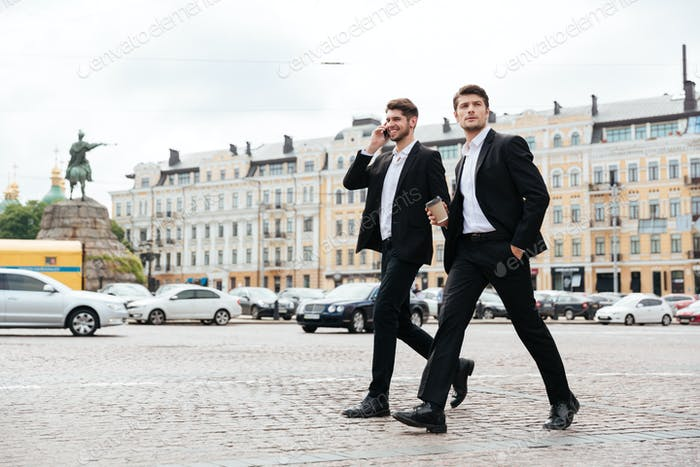 Two young businessmen walking and talking on mobile phone