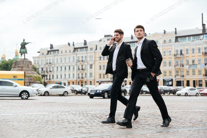 Dos jóvenes empresarios caminando y hablando por teléfono Móvil