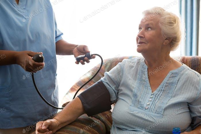 Медсестра, осматривая пациента в доме престарелых