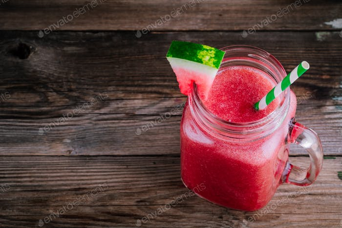 Watermelon smoothie in mason jar with mint on wooden background