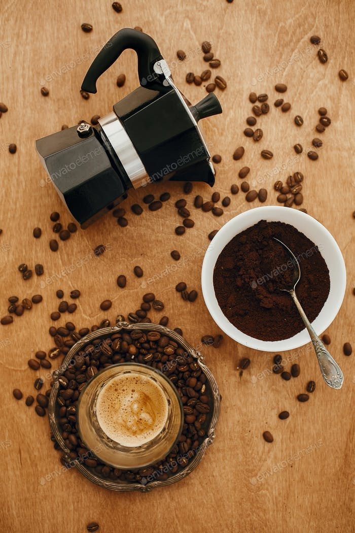 Coffee maker, aromatic beans, espresso on wooden table