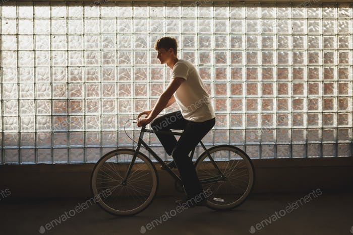 Young man in white t-shirt ridding bicycle with glass wall on background
