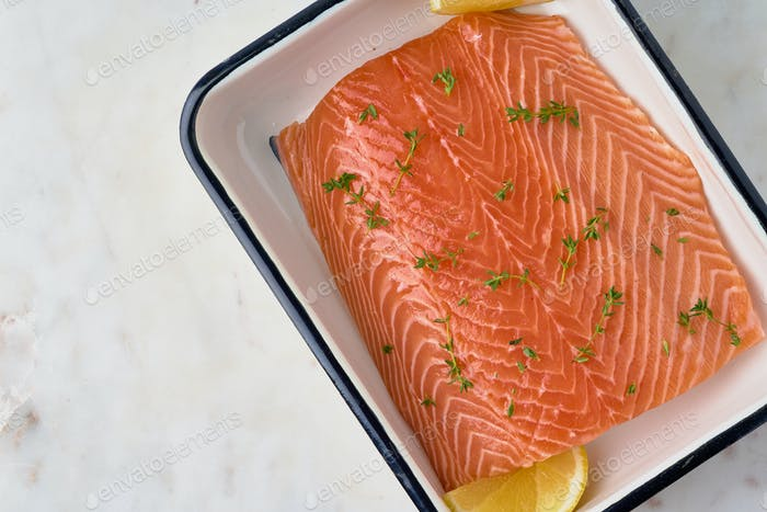 Raw salmon fillet with rosemary and lemon. Norwegian seafood cuisine. Humpback fillet