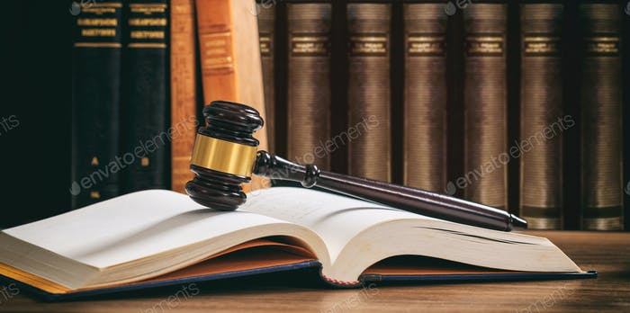Judge gavel on an open book, wooden desk, law books background