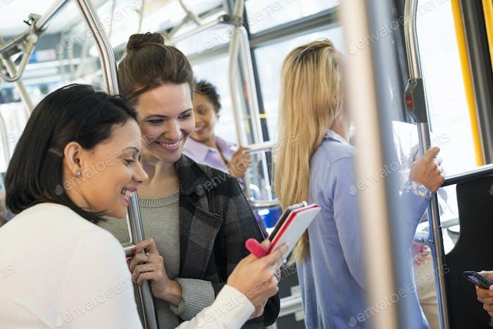 Menschen, Männer und Frauen in einem Stadtbus, zwei Frauen, die auf einem Handheld-Digital-Tablet suchen.